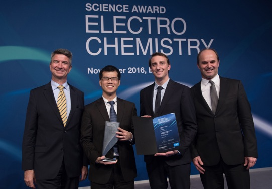 Will Chueh stands with award in hand with Volkswagen representatives